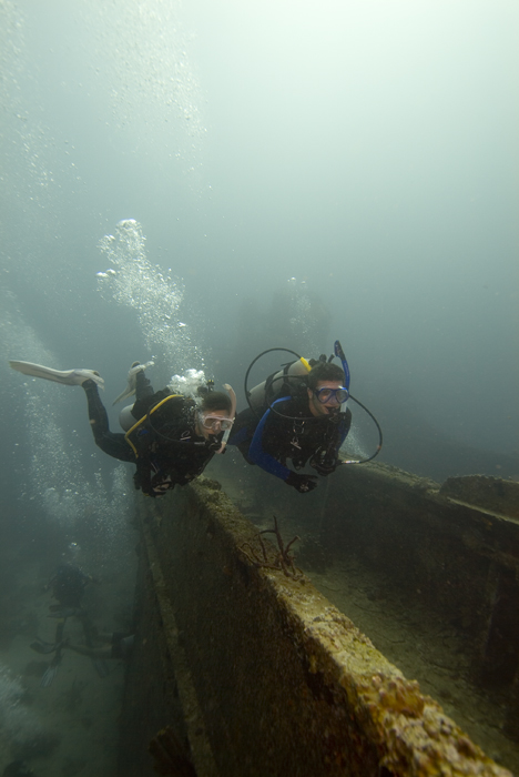 PADI Certified Assistant leading a student diver on a tour of a wreck