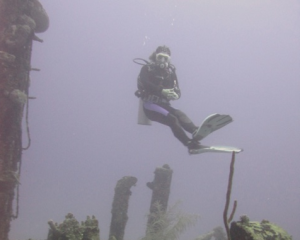 Weightless scuba diver hovering over a wreck